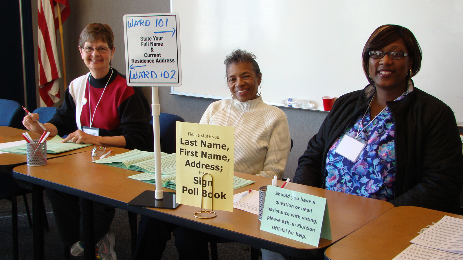 Three smiling election officials