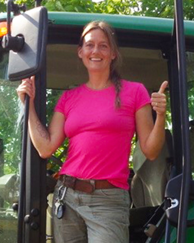 Laurel Franklin standing in the cab of a Parks Department vehicle.