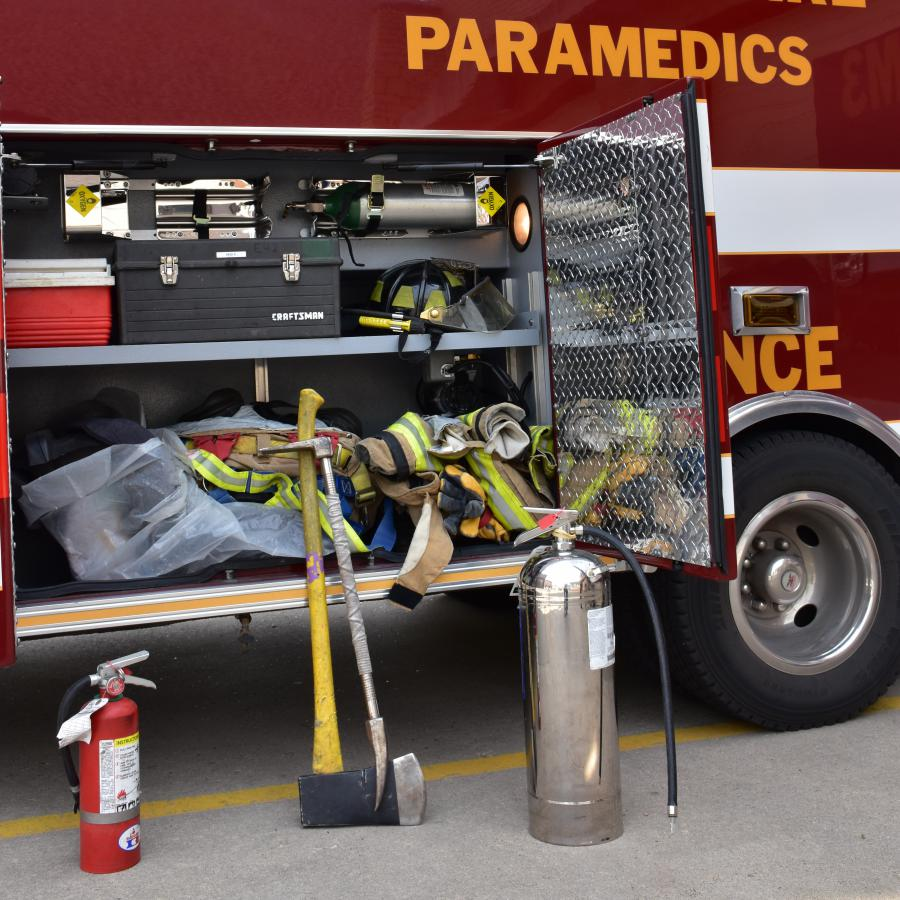 Extinguisher, axe, halligan, and water can next to ambulance