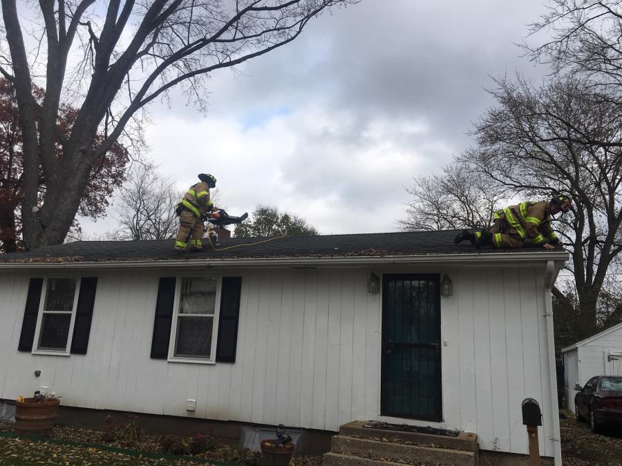 Firefighters cleaning roof