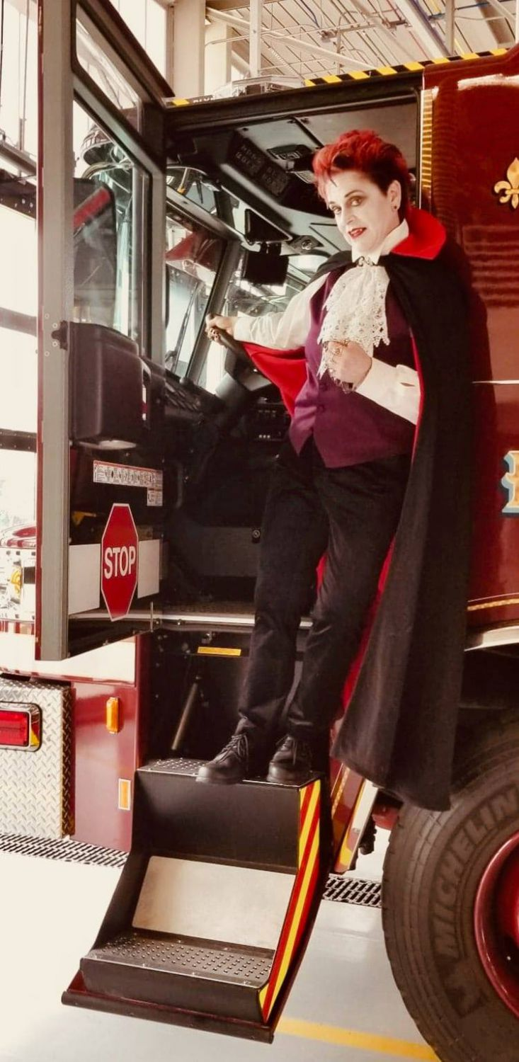 Firefighter Van Buskirk dressed as vampire by fire truck