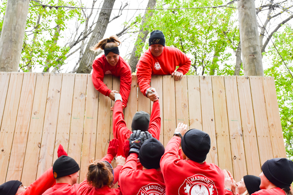 Two recruits are leaning over the top of a tall wall, and are pulling up a third recruit. A group of recruits at the bottom of the wall are helping left up the recruit.