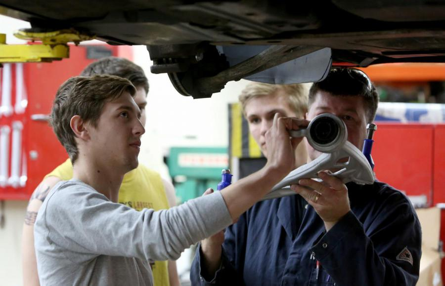 Student works with auto techer