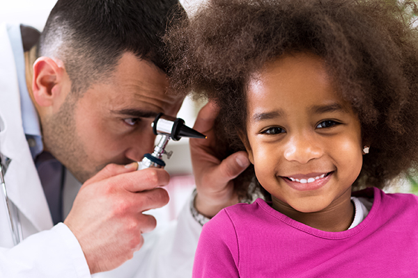 Doctor examining a young patient's ear
