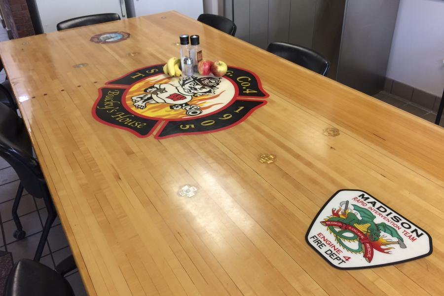 "Custom Tabletop - This custom table top displays the Station 4 ""Bucky's House"" logo, the MFD logo, and the patch for the Rapid Intervention Team, formerly based at Station 4."