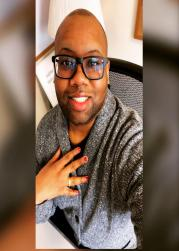 Mark Hargrove, a person with brown skin, wearing a grey sweater and glasses