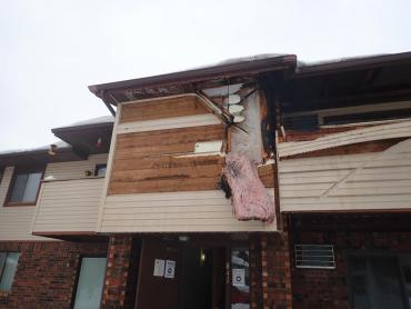 Damaged siding and balcony seen from the outside