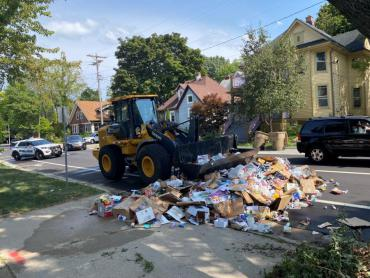 A loader scooping up recyclables dumped on the street. When loads on trucks catch on fire, they have to dump them on the street.