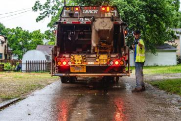 Streets Division operator giving a thumbs up while collecting trash in an alley off Monroe Street