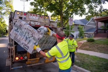 Two employees putting couch into garbage truck