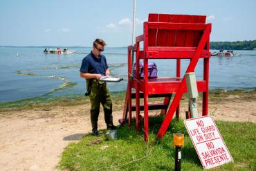 A person wearing waders standing on a beach next to a red lifeguard chair, holding a clipboard and pen
