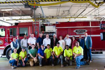City staff, vendors, governor, mayor pose for a group photo to celebrate new electric milestone