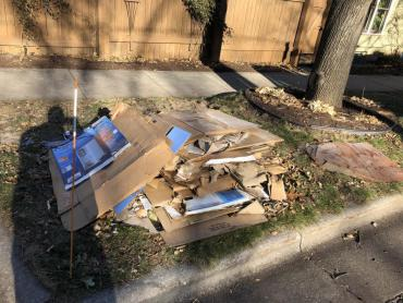 Stack of loose cardboard at the curb that is not bound, which means it may be very difficult for someone to collect