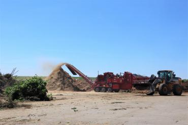 Industrial grinder making mulch at 121 E. Olin Ave.