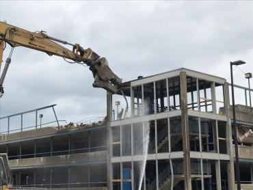 An excavtor equipped for demolition breaks off third floor guardrail and stairwell.