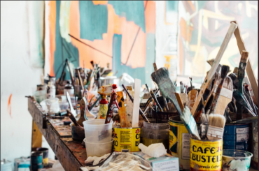 Paint brushes in coffee cans on a table with a mural in the background