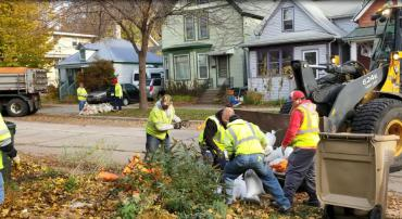City employees collecting sandbags from the curb in 2018