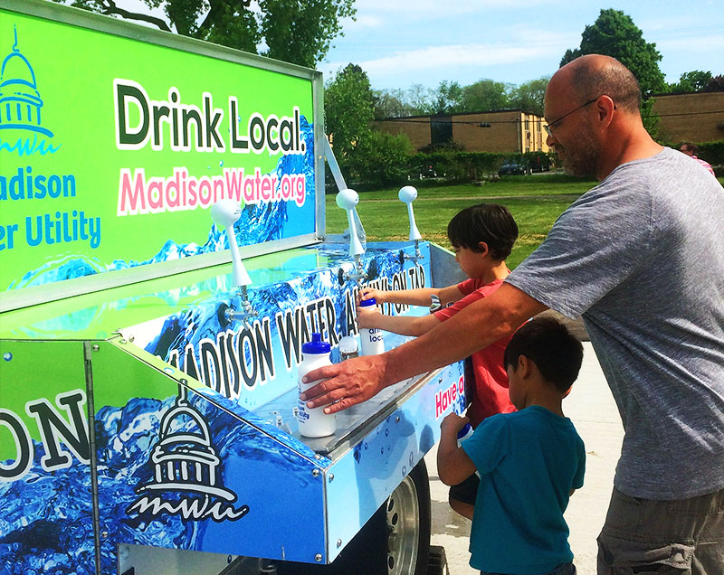 Man and children get water at the Water Wagon